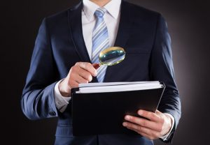28162252 - midsection of businessman examining documents with magnifying glass against black background