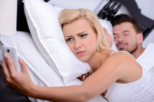 31329617 - young blonde woman, use phone in while her husband sleeps